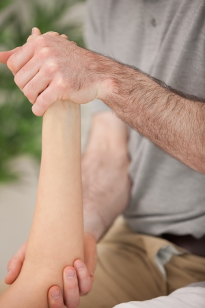 muscle retraining: Ankle and elbow of a patient being manipulated in a medical room Stock Photo