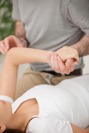 upper limb: Physiotherapist moving the arm of a woman in a room