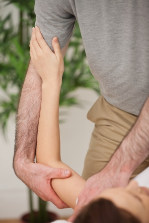 muscle retraining: Brunette woman being manipulated by a doctor in a medical room