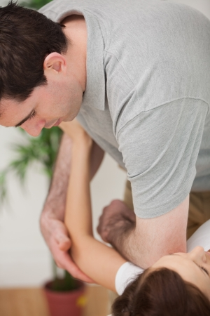 mobilization: Serious osteopath placing his elbow of the shoulder of a patient in a room Stock Photo