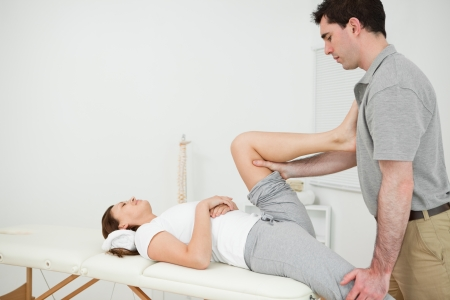 Osteopath stretching the leg of his patient in his medical room Stock Photo - 16204401