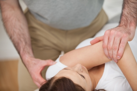 Osteopath making a joint mobilisation in his medical office photo