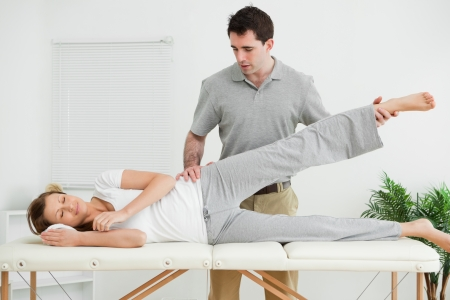 neuromuscular reeducation: Serious practitioner rising the leg of his patient in his room