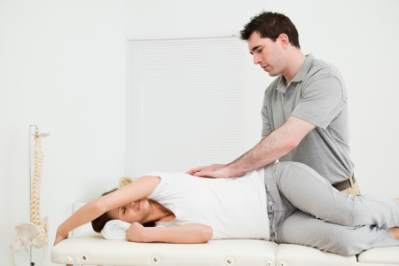 spinal conditions: Brunette woman lying on the side while being massaged in a medical room Stock Photo