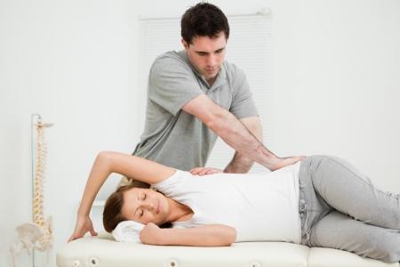 osteopata: Oste�pata cruz�ndose de brazos mientras le da masaje a una mujer en su consultorio m�dico Foto de archivo