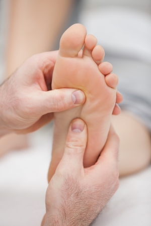Reflexology massage being made in a room photo