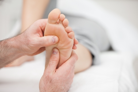 muscle retraining: Patient receiving a foot massage in a room Stock Photo