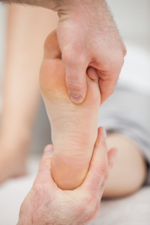 muscle retraining: Doctor pressing his thumb on a foot in a room