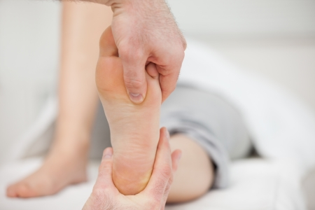 chiropodist: Practitioner placing his thumb on a foot in a medical room