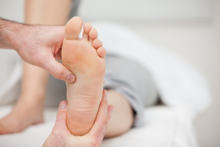 Doctor holding the foot of a woman in his office Stock Photo - 16203977