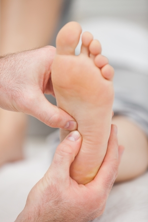 neuromuscular reeducation: Two thumbs massaging a foot in a room