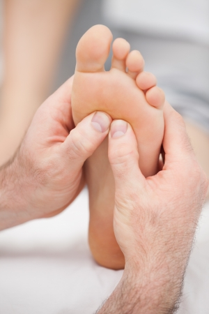 foot pain: Hands massaging a foot on a medical table Stock Photo