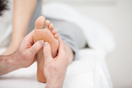 neuromuscular reeducation: Foot being massaged on a medical table in a room