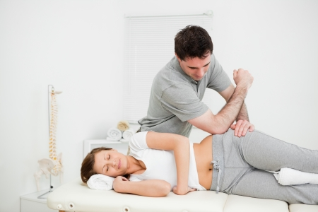 osteopath: Doctor using his elbow to massage the hip of a woman in a room