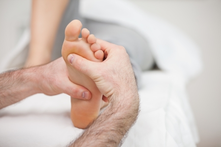 neuromuscular reeducation: Man using his two hands to massage a foot in a room