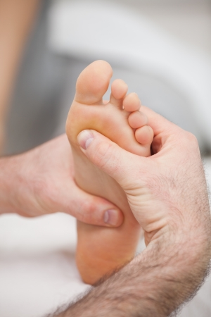 foot doctor: Sole of foot being massaged in a medical room