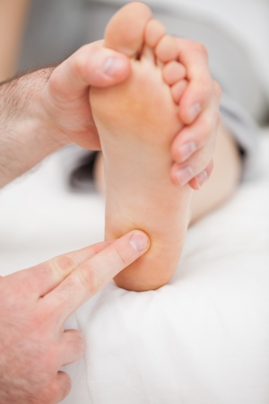 Doctor massaging the ball of the foot in a room Stock Photo - 16204041