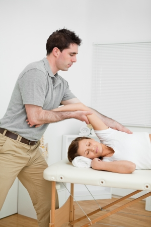 spinal conditions: Serious doctor making a manual stretching in a medical room Stock Photo