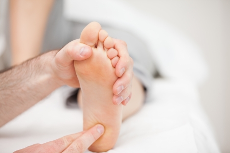 foot pain: Doctor using his fingertips to touch the ball of a foot in a room
