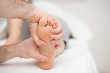 Two hands holding a foot in a room Stock Photo - 16203650