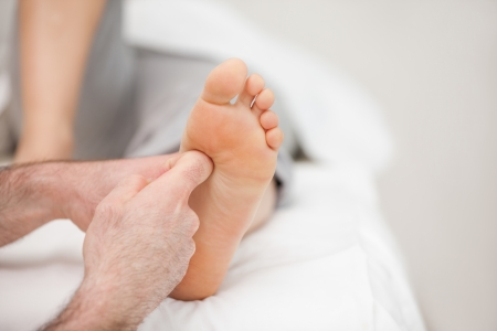 touching toes: The side of a foot being massaged in a room
