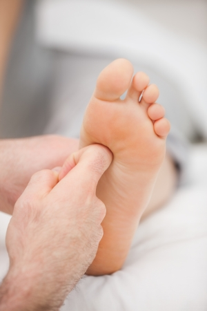 neuromuscular reeducation: Finger massaging a foot in a room Stock Photo