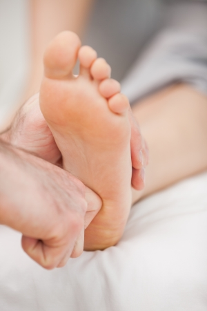 neuromuscular reeducation: The ball of a foot being massaged in a room Stock Photo