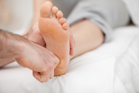 muscle retraining: Ball of a foot being touched by a doctor in a room