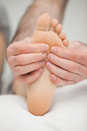 Fingers palpating the sole of a foot in a room Stock Photo - 16204539