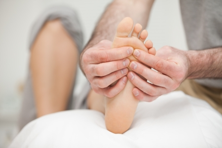 neuromuscular reeducation: Sole of a foot being touched by a doctor in a room Stock Photo