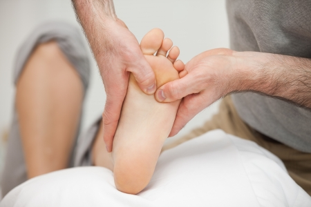 muscle retraining: Chiropodist touching the foot of a woman in a medical room