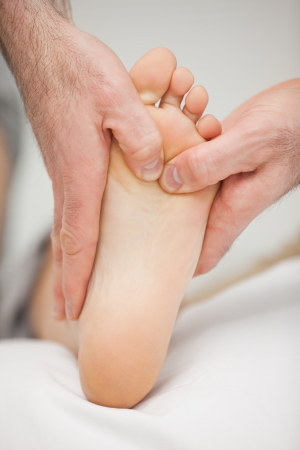 chiropodist: Chiropodist massaging the foot of a patient in a medical room