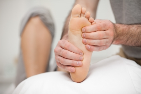 neuromuscular reeducation: Chiropodist palpating the sole of the foot of a patient in his office