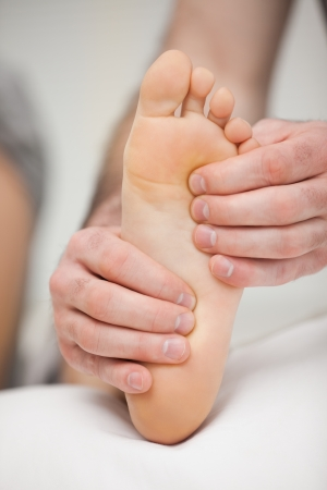 neuromuscular reeducation: Fingertips touching the sole of a foot in a room