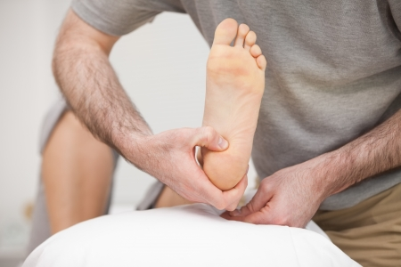 Doctor placing the foot of a patient on a pillow in his office Stock Photo - 16207151