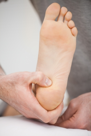 muscle retraining: Foot being raised by a chiropodist in a room Stock Photo