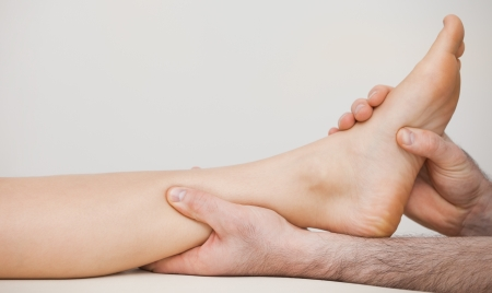 neuromuscular reeducation: Chiropodist holding the ankle of a patient in his medical room