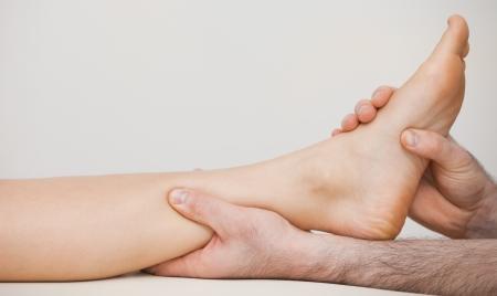 tendones: Chiropodist que sostiene el tobillo de un paciente en su habitaci�n m�dica