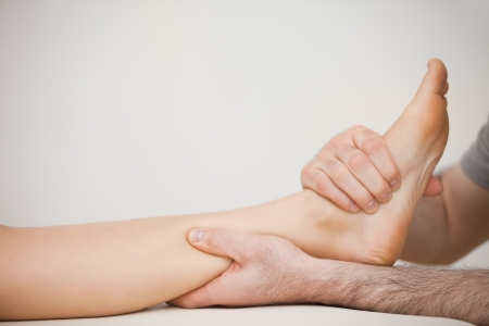neuromuscular reeducation: Muscle of a foot being massaged in a room