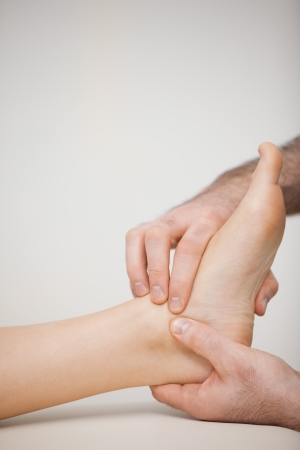 chiropodist: Doctor massaging the side of a foot in a medical room
