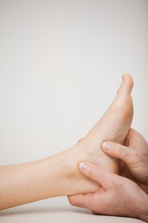 Two thumbs being placed on the side of a foot in a medical room Stock Photo - 16203425