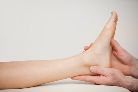 muscle retraining: Chiropodist holding the foot of a patient in a medical room