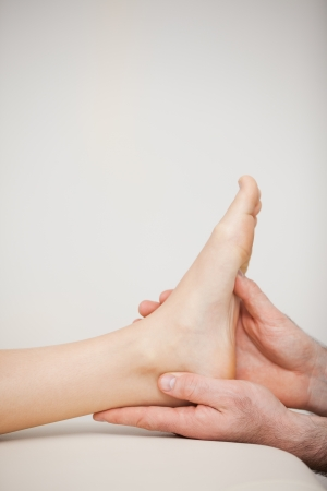 joint mobilization: Close-up of a foot being held by a doctor in a medical room