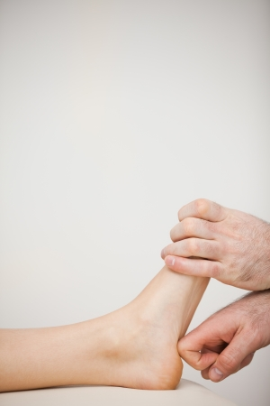 chiropodist: Chiropodist using his index finger to massage a foot in a medical room
