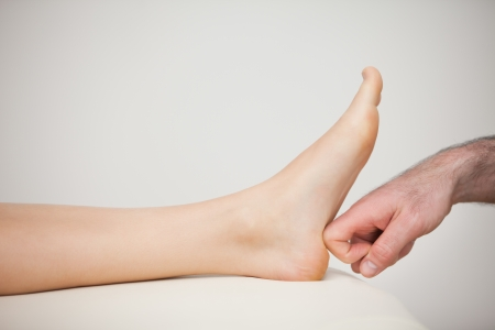 chiropodist: Forefinger touching a barefoot in a room