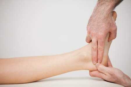 joint mobilization: Chiropodist placing two fingers on a foot indoors