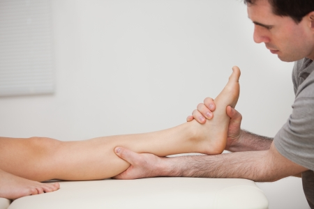 tendons: Serious physiotherapist holding the foot of a patient indoors