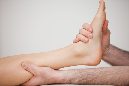 tendons: Foot being held by a doctor indoors