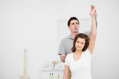 Serious osteopath raising the arm of a patient in a medical room Stock Photo - 16202461