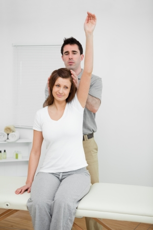 Peaceful woman raising her arm while being manipulated in a medical room Stock Photo - 16204200